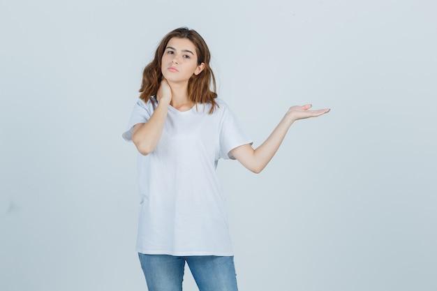 Jovem fingindo mostrar algo enquanto segura a mão no pescoço em uma camiseta, jeans e parece confiante, vista frontal.