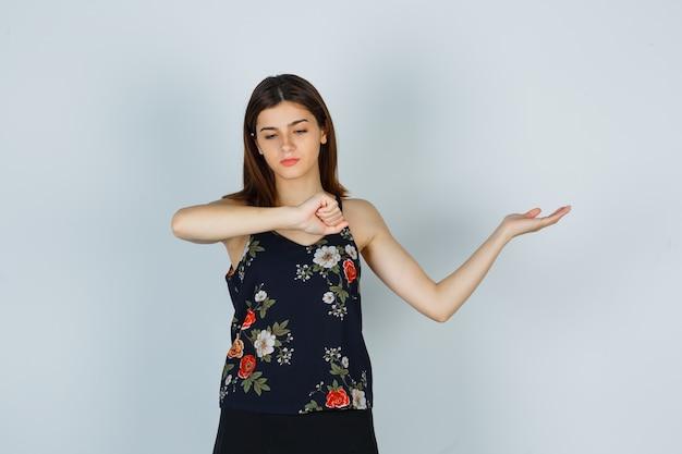 Jovem fingindo olhar o relógio no pulso, espalhando a palma da mão para o lado na blusa, saia e parecendo pensativa. vista frontal.
