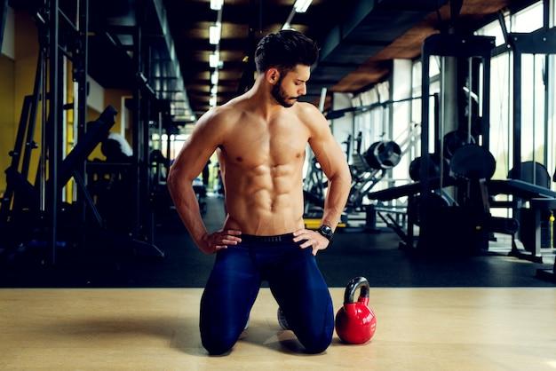Jovem fisiculturista ativo está exercitando com um kettlebell no ginásio.