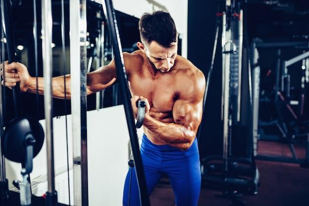 Jovem fisiculturista fazendo exercício para bíceps