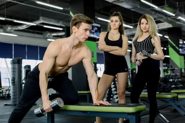 Jovem fisiculturista malhando com pesos do dumbbell na academia, mostrando o exercício para duas jovens mulheres no fundo.
