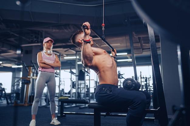 Jovem fisiculturista masculina fazendo exercício de peso pesado, enquanto sua namorada o observava
