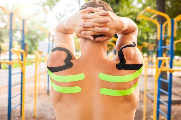 Jovem fisiculturista profissional caucasiano irreconhecível com fitas cinesiológicas pretas e verdes em ombros musculosos, posando em campo esportivo