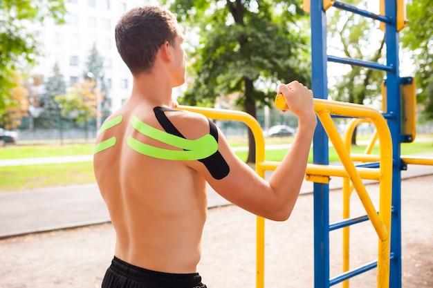 Jovem fisiculturista profissional caucasiano irreconhecível com fitas elásticas pretas e verdes nos ombros, posando em campo esportivo