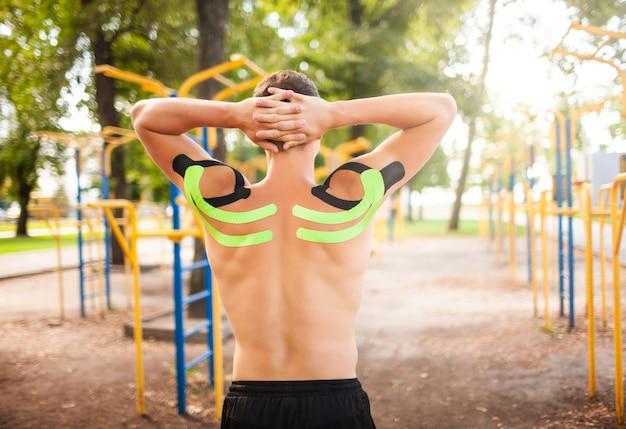 Jovem fisiculturista profissional irreconhecível com fitas cinesiológicas pretas e verdes