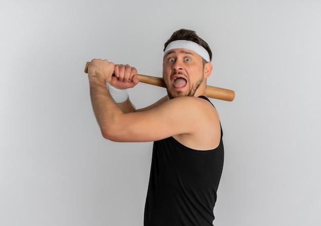 Jovem fitness com bandana e medalha de ouro balançando um taco de beisebol assustado em pé sobre um fundo branco