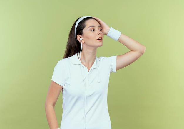 Jovem fitness com bandana olhando para o lado com expressão confiante em pé sobre a parede de luz Foto gratuita