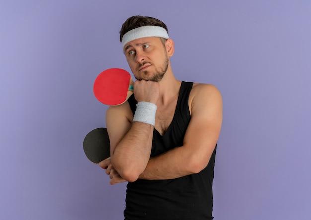 Jovem fitness com bandana segurando duas raquetes de tênis de mesa olhando para o lado com expressão pensativa em pé sobre a parede roxa