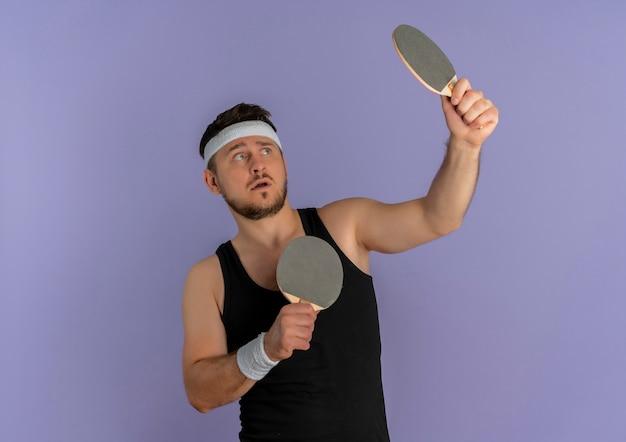 Jovem fitness com bandana segurando duas raquetes de tênis de mesa, parecendo confuso em pé sobre a parede roxa