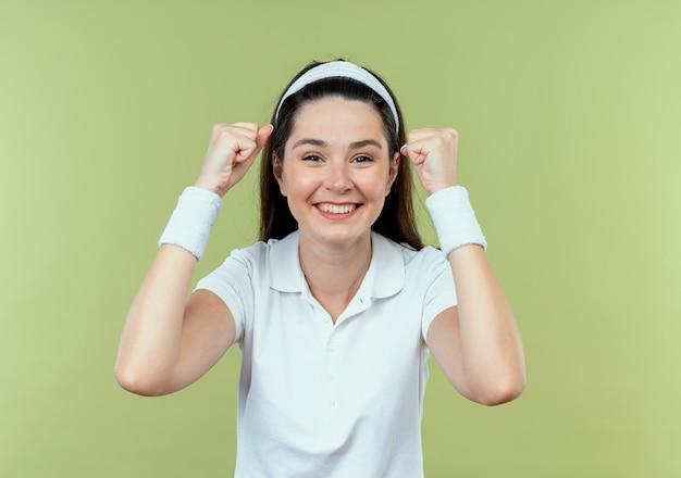 Jovem fitness com fita para a cabeça cerrando os punhos feliz e animada em pé sobre a parede de luz