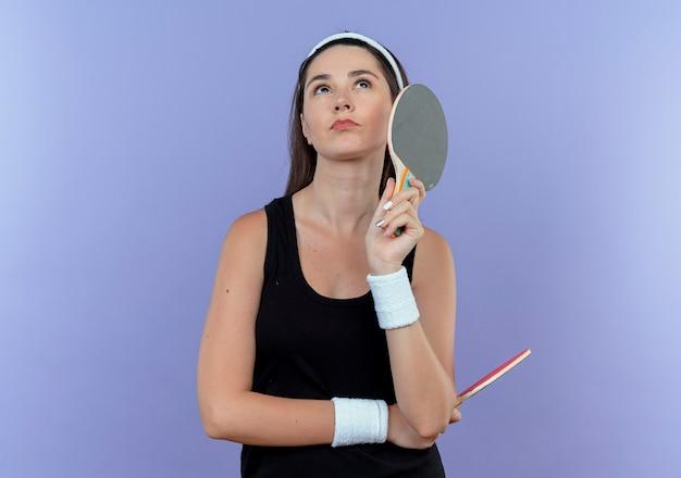 Jovem fitness com uma bandana segurando raquetes de tênis de mesa, olhando para cima confusa em pé sobre a parede azul