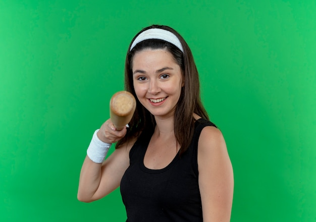 Jovem fitness com uma bandana segurando um taco de beisebol apontando para a câmera e sorrindo em pé sobre um fundo verde