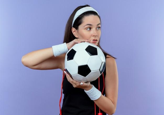 Jovem fitness com uma faixa na cabeça e pular corda no pescoço segurando uma bola de futebol, olhando para o lado com expressão confiante em pé sobre a parede azul