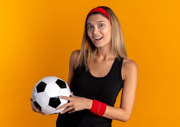 Jovem fitness em roupa esportiva preta e bandana vermelha, segurando uma bola de futebol, surpresa com o rosto feliz sobre laranja