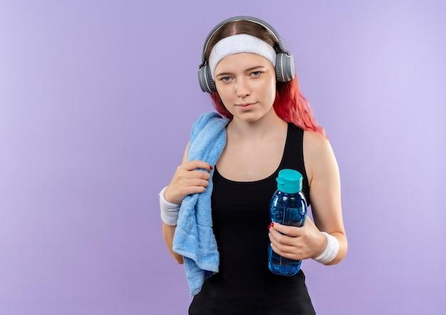 Jovem fitness garota em roupas esportivas com fones de ouvido e toalha no pescoço segurando uma garrafa de água em pé sobre a parede roxa