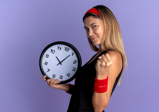 Jovem fitness garota em roupas esportivas pretas e bandana vermelha segurando o relógio de parede cerrando os punhos com uma cara séria em pé sobre a parede azul