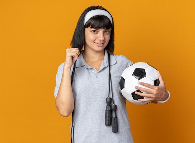 Jovem fitness garota usando bandana e pular corda em volta do pescoço segurando uma bola de futebol, olhando para a câmera, sorrindo confiante levantando o punho em pé sobre fundo laranja