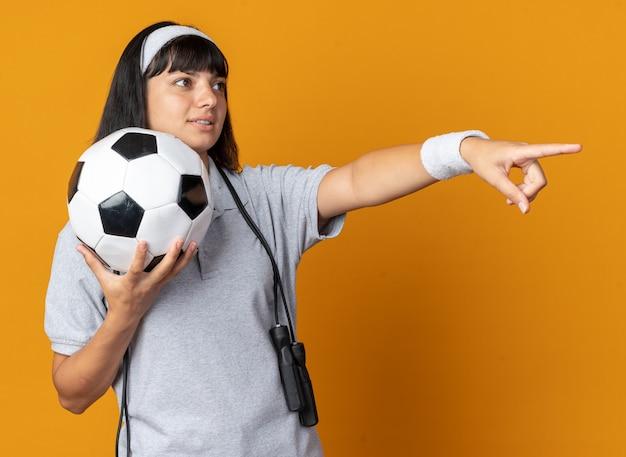 Jovem fitness garota usando bandana e pular corda em volta do pescoço segurando uma bola de futebol, olhando para o lado com um sorriso no rosto apontando com o dedo indicador para algo em pé sobre um fundo laranja