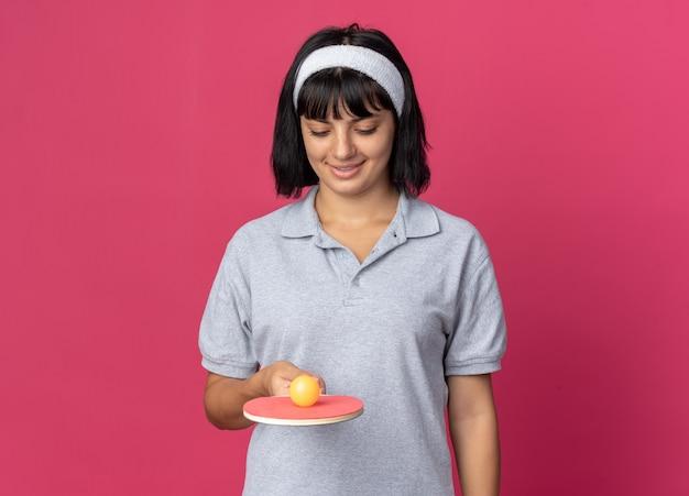 Jovem fitness garota usando uma bandana segurando uma raquete e uma bola de tênis de mesa, sorrindo com uma cara feliz em pé sobre um fundo rosa