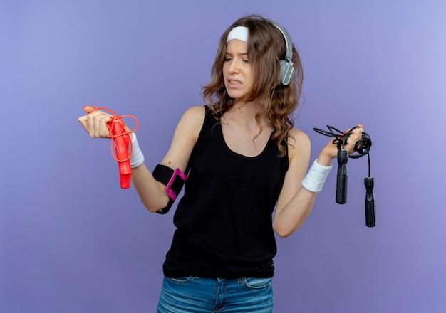Jovem fitness girl em roupa esportiva preta com tiara segurando duas cordas de pular lookign confusa tentando fazer uma escolha em pé sobre a parede azul