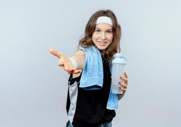 Jovem fitness girl em sportswear preto com tiara e toalha ao redor do pescoço segurando uma garrafa de água, fazendo gesto de venha cá com a mão sorrindo em pé sobre a parede branca