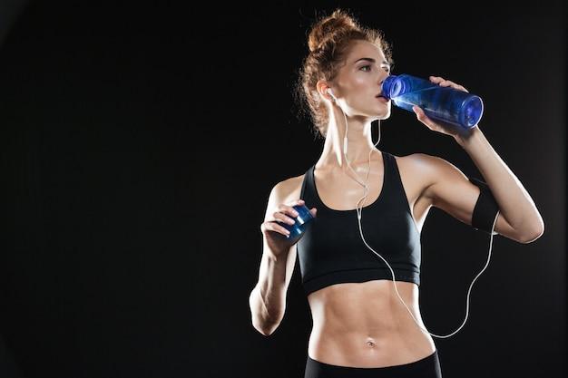Jovem fitness mulher bebendo água