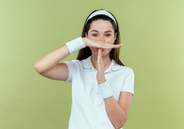 Jovem fitness mulher com fita para a cabeça fazendo um gesto com as mãos em pé sobre a parede de luz