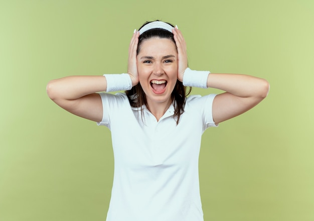 Jovem fitness mulher com uma bandana louca, louca, gritando, fechando os ouvidos com as mãos em pé sobre a parede de luz