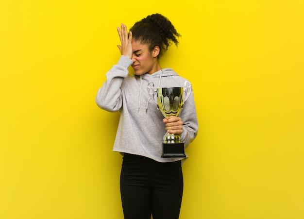 Jovem fitness mulher negra esquecida, perceber algo. segurando um troféu.