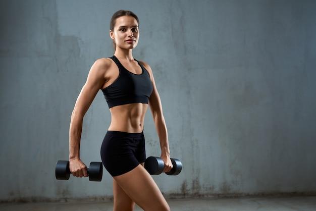Jovem fitness mulher posando com halteres