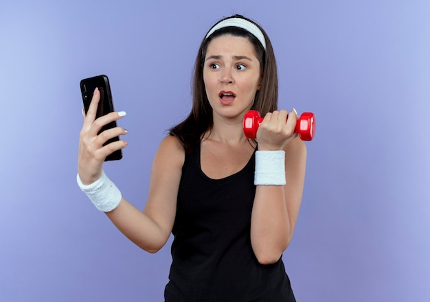 Jovem fitness na mesa da bandana segurando um smartphone fazendo exercícios com halteres, parecendo confusa em pé sobre a parede azul