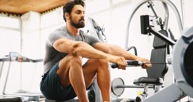 Jovem fitness usando máquina de remo na academia