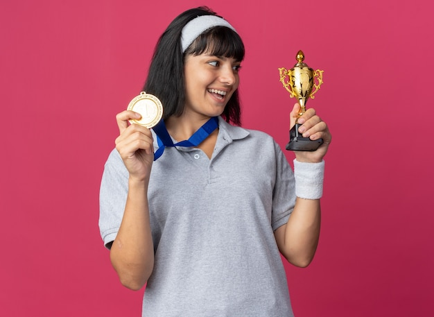 Jovem fitness usando uma faixa na cabeça com medalha de ouro em volta do pescoço segurando um troféu olhando para ele feliz e animada em pé sobre a rosa