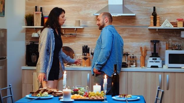 Jovem flertando durante encontro romântico com mulher, em casa, na cozinha durante o jantar. esposa frustrada saindo do quarto chateada enquanto o marido bebe impassível uma taça de vinho tinto