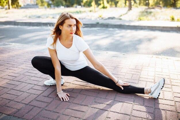 Jovem flexível, esticada antes do treino,