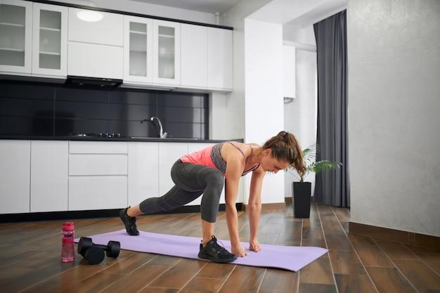 Jovem flexível se espreguiçando em casa
