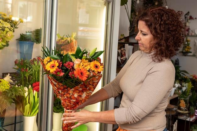Jovem florista, arranjos de flores em uma floricultura.