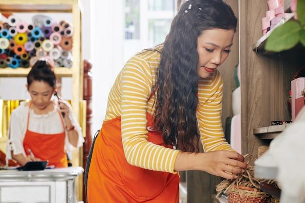 Jovem florista asiática séria pegando corda de juta da prateleira para decorar o buquê para o cliente