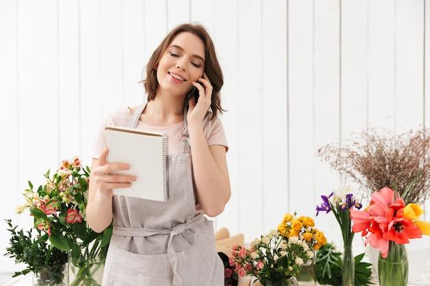 Jovem florista em pé perto de uma mesa com flores diferentes e ligando para clientes com bilhetes nas mãos