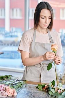Jovem florista feminina no avental em pé junto à mesa e olhando para a rosa pálida rosa nas mãos durante o trabalho