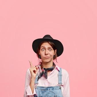 Jovem florista indignada em roupas casuais, apontando para cima com o dedo da frente, com expressão facial intrigada