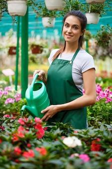 Jovem florista linda regando flores.