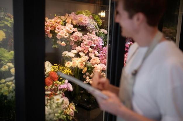 Jovem florista tomando notas das flores na loja