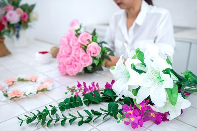 Jovem florista trabalhando organizando flores artificiais
