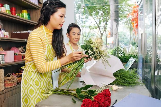 Jovem florista vietnamita séria fazendo buquê sob o controle de seu experiente colega