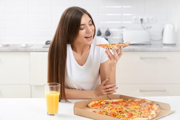 Jovem fofa comendo pizza saborosa