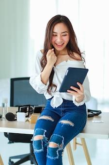 Jovem, fofa e bonita vendedora asiática olhando para a tela do computador tablet e me sentindo muito feliz e animada ao ver o pedido do cliente. venda pela internet e conceito de marketing online.