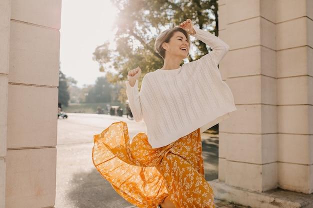 Jovem fofa feliz e sorridente em um vestido amarelo estampado e um suéter branco de tricô em um dia ensolarado de outono