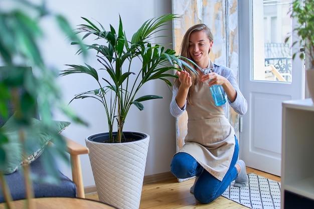 Jovem fofa feliz sorrindo atraente jardineiro com avental regando plantas domésticas com spray