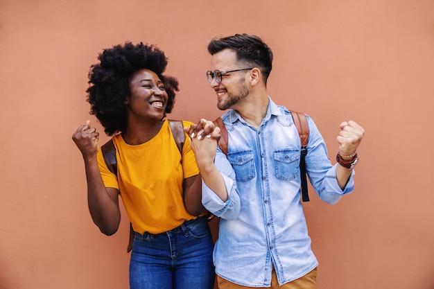 Jovem fofo casal multicultural muito feliz de mãos dadas e punhos em pé na rua.